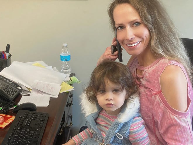 Elizabeth Griem, 33, of Grosse Pointe holds her 2-year-old daugter, Aaliyah, on her lap while working to make COVID-19 vaccine appointments for people eligible for shots in Michigan.