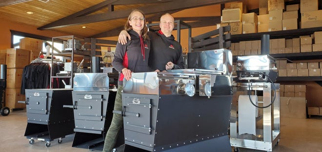 Angela and Jim Schumacher stand next to their company's Dauntless Evaporator. The product, which is used to boil maple sap, is popular with maple syrup hobbyists.