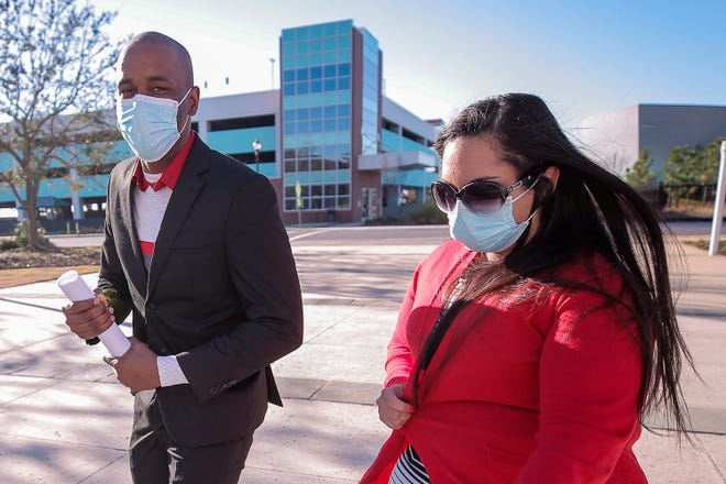 Moss Point Mayor Mario King, left, and his wife, Natasha King, head toward the federal courthouse in Gulfport, Miss., Wednesday, Feb. 24, 2021, to plead guilty to a charge of conspiring to defraud the federal government.