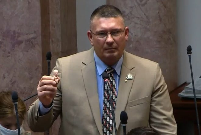 Rep. Bill Wesley, R-Ravenna, holds up a plastic fetus during a debate on a constitutional amendment to declare no right to an abortion in Kentucky.