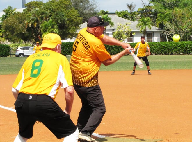 Sand Bar's Pat Comerford drives the ball to the opposite field for one of his two hits against Mango's.
