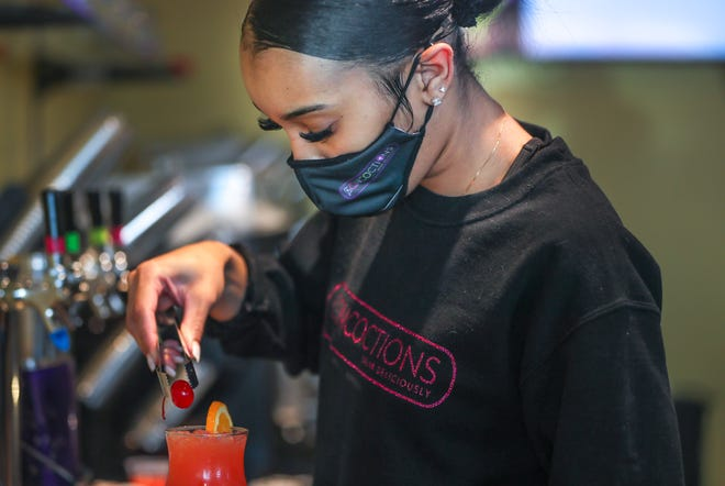 Concoctions manager Hyleah Pulley, 23, adds a cherry on top of a Rum Punch Tuesday.