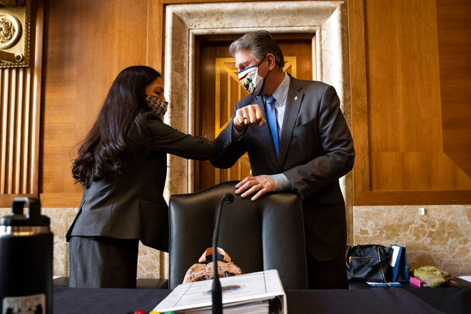 Sen. Joe Manchin, D-W.Va., greets Rep. Deb Haaland, D-N.M., before the start of the Senate Committee on Energy and Natural Resources hearing on her nomination to be Interior Secretary, Tuesday, Feb. 23, 2021, on Capitol Hill in Washington.