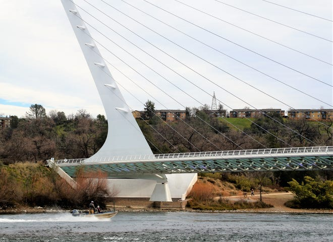 A motorboat travels under the Sundial Bridge in Redding on Thursday, Feb. 25, 2021. A new study refutes a previous report that said lights from the Sundial Bridge were creating conditions that killed baby salmon in the Sacramento River.