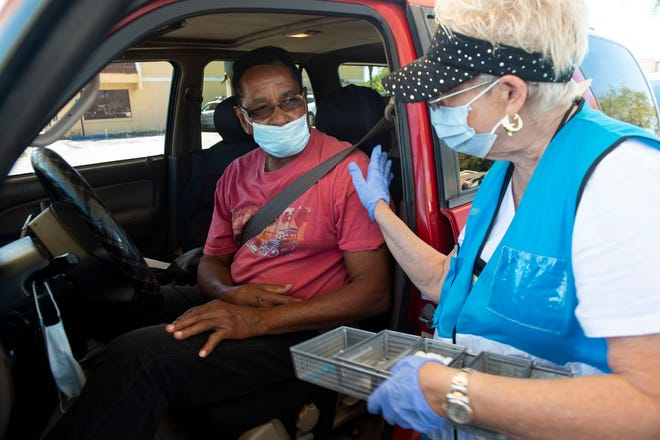 Dori Sutherland (right), RN, explains information regarding Robert Newman's Moderna COVID-19 vaccine during a vaccination outreach offered by the Florida Department of Health Martin County and the NAACP of Martin County on Thursday, Feb. 25, 2021, along Southeast Martin Luther King Jr. Boulevard in Stuart.