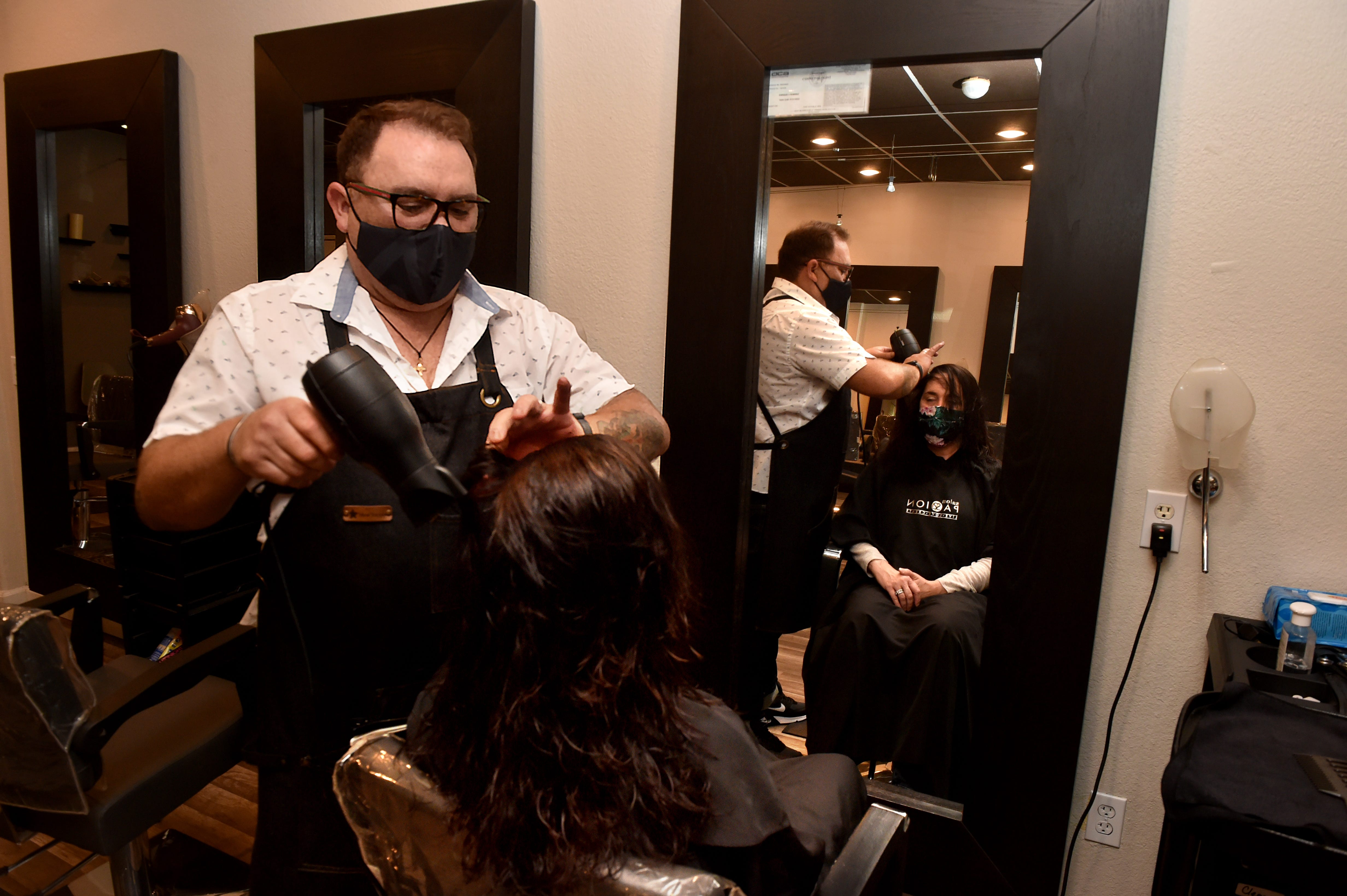 Enrique Ramirez, owner of Salon Passion in Camarillo, styles the hair of Leslie Kaplan on Wednesday, Feb. 24, 2021, as Ramirez and his staff work to keep the business going through the pandemic. After so many ups and downs in 2020, the salon owner nearly closed his business for good but now expects to stay open as more people get vaccinated.