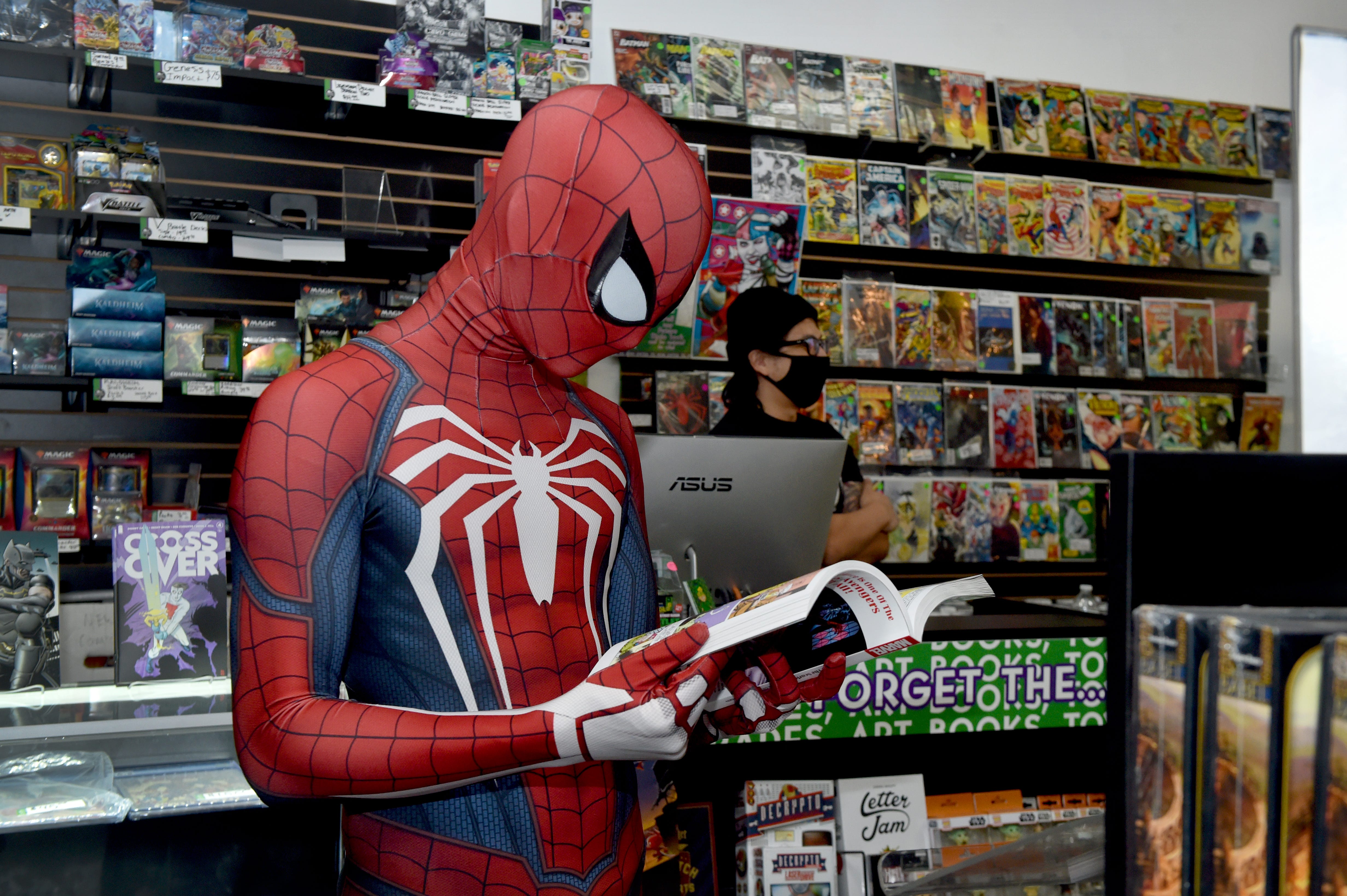 Aaron Riven, of Los Angeles, dressed as Spiderman, browses through a graphic novel during a visit to Arsenal Comics & Games in Newbury Park on Wednesday, Feb. 24, 2021. Store owner Timmy Heague, who owns a second shop in Ventura, said after struggling through a break-in at the Newbury Park store and the pandemic, 2020 was the business' best year ever in sales.