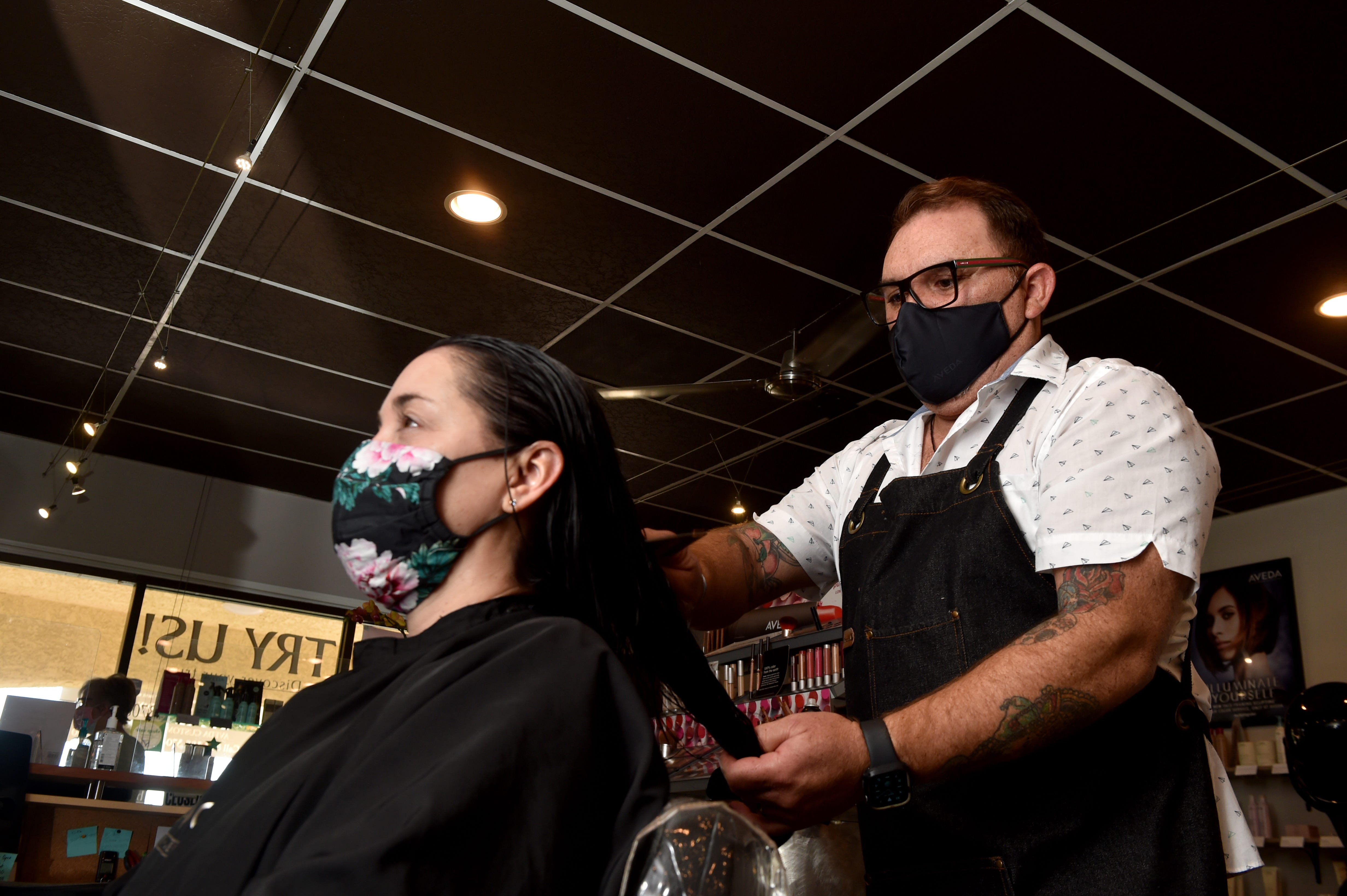 """Enrique Ramirez, owner of Salon Passion in Camarillo, styles the hair of Leslie Kaplan on Wednesday, Feb. 24, 2021, as Ramirez and his staff work to keep the business going through the pandemic. The salon owner described the last year as a """"roller coaster."""""""