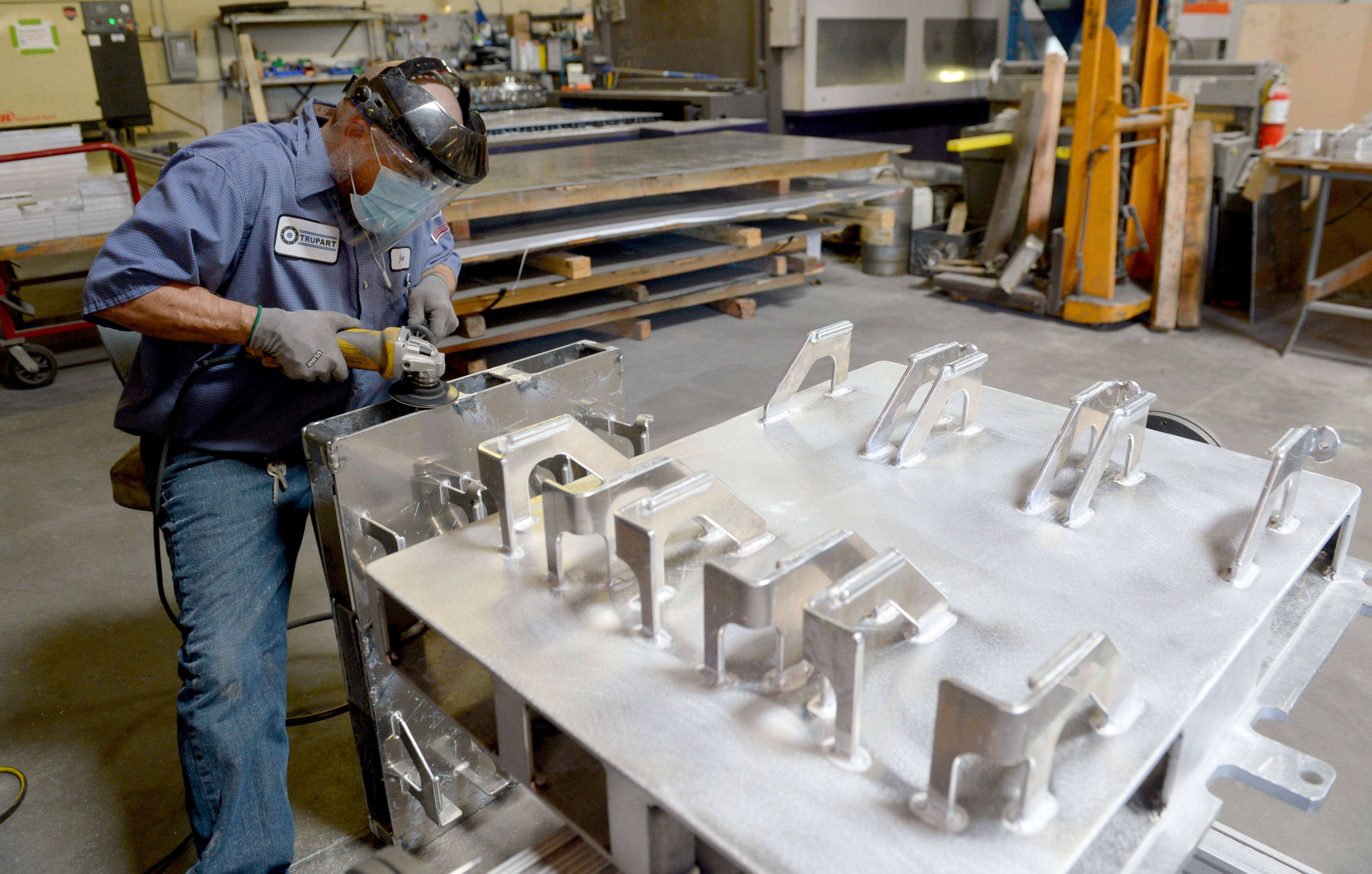 Jesse Perez cleans up metal pallets at Trupart Manufacturing on Tuesday, Feb. 23, 2021. Trupart is a design, prototype, fabrication and production firm in Ventura that after nearly 50 years in business narrowly avoided closing its doors during the COVID-19 pandemic.