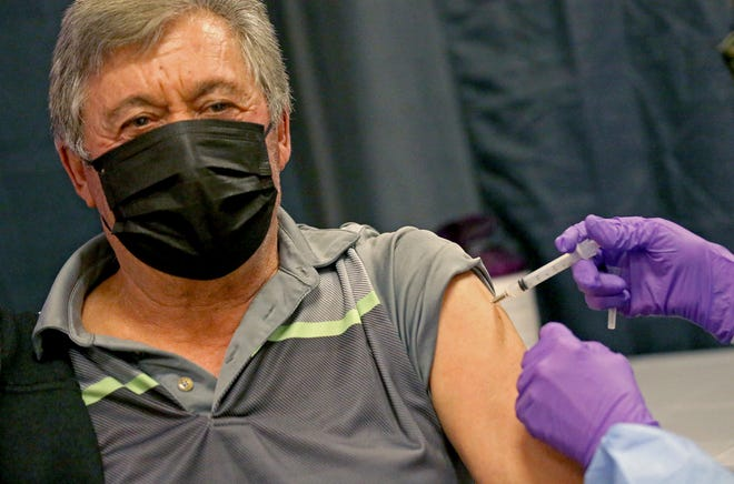 Antonio Loffa gets his COVID-19 vaccine at a mass vaccination site at the Natick Mall on Wednesday in Natick, Mass.
