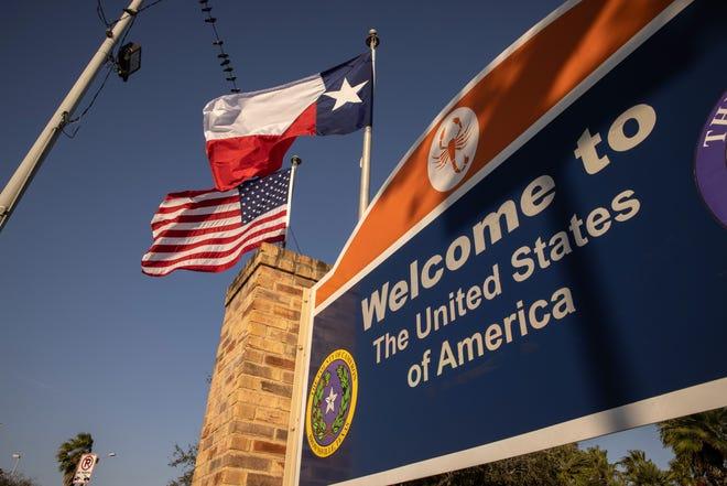 Las banderas de Estados Unidos y Texas sobrevuelan Brownsville, Texas, el 24 de febrero de 2021, cerca de la frontera entre Estados Unidos y México.