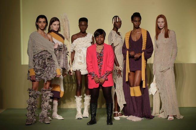 Fashion designer Gisele Claudia Ntsama poses with models during the Black Lives Matter Fall/Winter 2021/22 collection collective show, presented in Milan, Italy, Wednesday, Feb. 17, 2021.