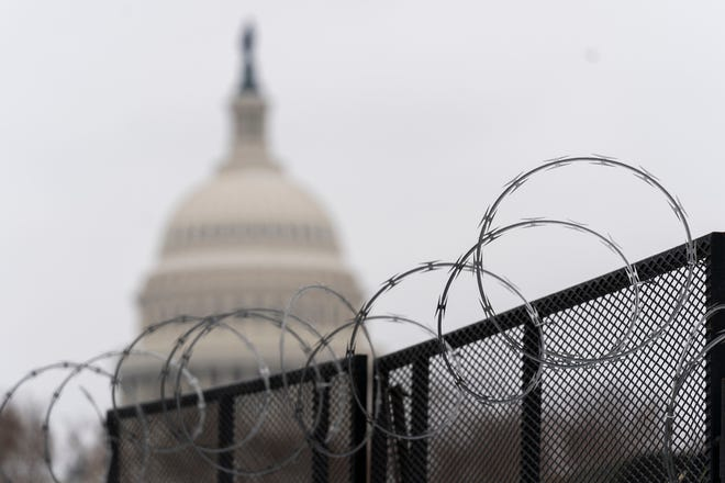 The U.S. Capitol is seen behind the razor fence around the U.S. Capitol, Thursday, Feb. 18, 2021.