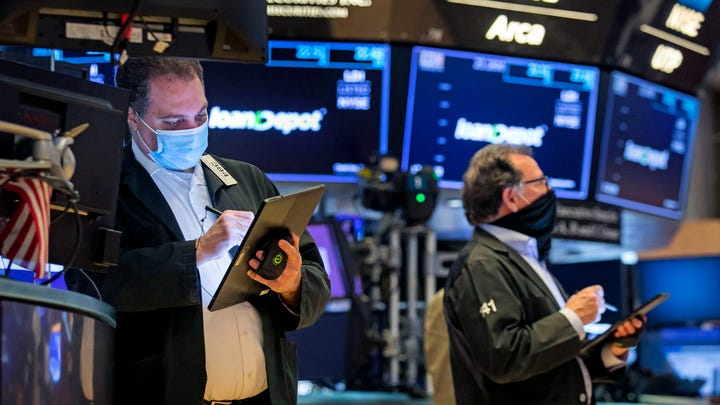 In this photo provided by the New York Stock Exchange, traders work on the floor, Monday Feb. 22, 2021. Investors remain focused on the future of global economies badly hit by COVID-19 and the potential for more stimulus to fix them.