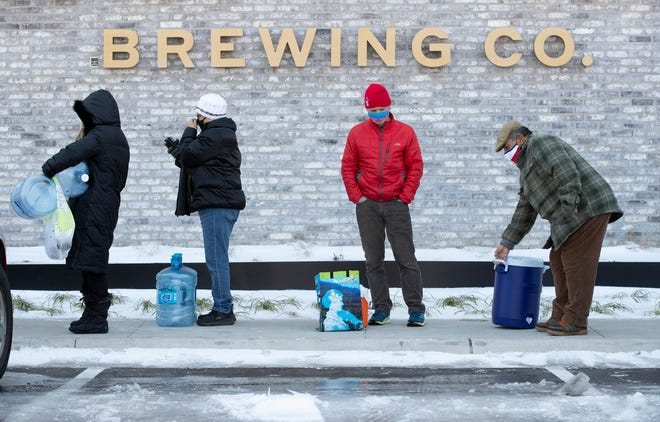 Tina Hall, from left, Susana Sosa, Jim Sefcik and Chris Sosa wait in line to fill up their containers with water at Meanwhile Brewing Co. on Feb. 19 during a citywide boil water notice caused by the winter storm.