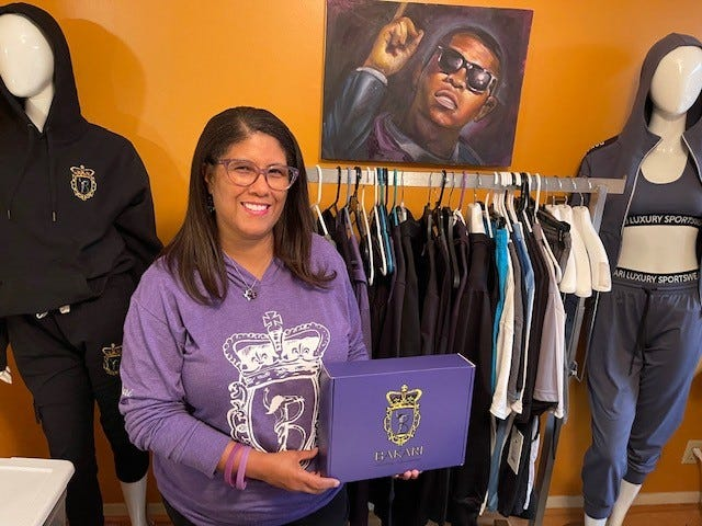 Jill Henderson shows some of the clothing that Bakari Luxury Sportswear has started to produce. The line was created by her son Bakari, who was killed in Greece.