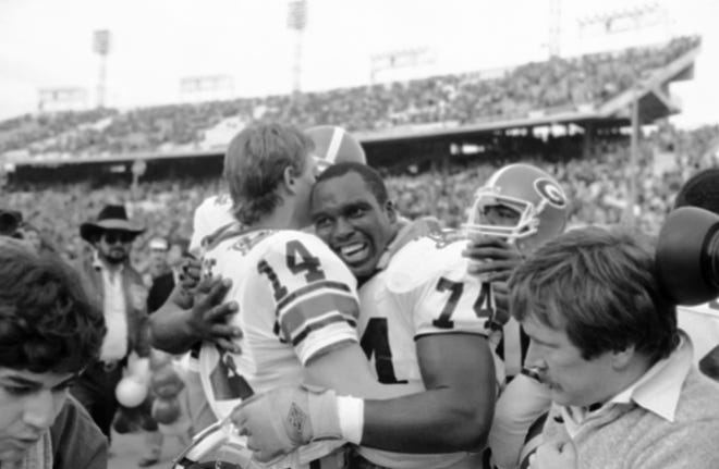 University of Georgia players Terry Hoage (14) and Guy McIntyre (74) embrace after their 10-9 victory over Texas in the Cotton Bowl Classic in Dallas, Monday, Jan. 3, 1984. (AP Photo/Bill Haber)