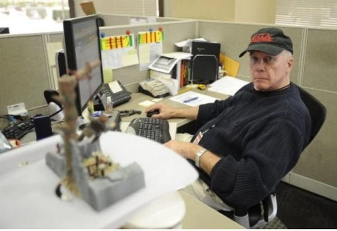 John Futch, wearing a University of Georgia cap in a newsroom in California, had his start in journalism at the Athens Daily News.