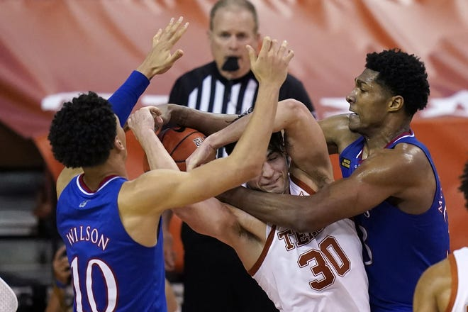 Texas forward Brock Cunningham fights for a rebound with Kansas' Jalen Wilson, left, and David McCormack during overtime of the Longhorns' victory Tuesday.