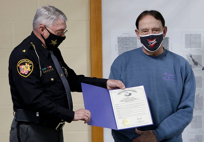 Sheriff E. Wayne Risner presents a proclamation from the Ohio Attorney General Dave Yost to retired Chief Deputy Carl Richert for his 40 years of service to the Ashland County Sheriff's Office at the 2020 Ashland County Sheriff Awards ceremony on Thursday, Feb. 25, 2021. TOM E. PUSKAR/TIMES-GAZETTE.COM