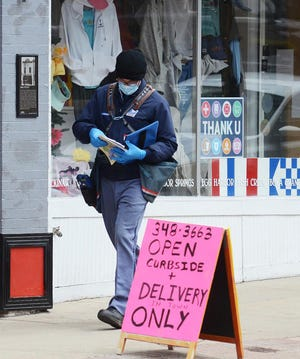 A United States Postal Service employee delivers mail in downtown Petoskey in the spring of 2020. Many businesses in the area were forced to shift directions as a result of the novel coronavirus, which his the area in March 2020.