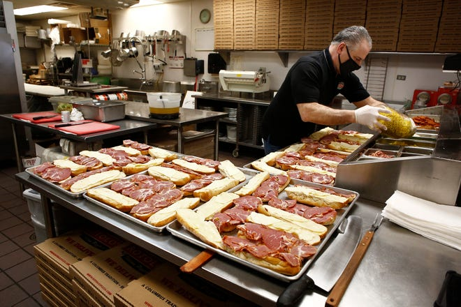 Dominic Rotolo replenishes toppings at the family-owned Rotolo's Pizza near Grandview Heights. The business recently was the subject of a short YouTube film related to its jingle from 20 years ago.