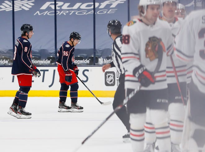 Blue Jackets defenseman Zach Werenski, left, and forward Jack Roslovic skate toward the team bench while the Chicago Blackhawks celebrate Carl Soderberg's empty-net goal that clinched a 2-0 victory over Columbus on Thursday.