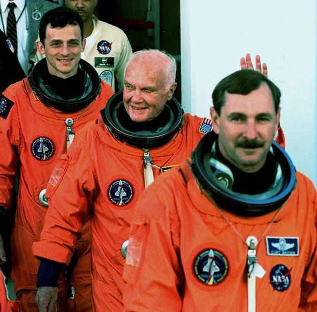 Sen. John Glenn, center, D-Ohio, leaves the Operations and Checkout Building along with Commander Curt Brown, right, and Spanish Mission Specialist Pedro Duque Thursday morning Oct. 29, 1998 for a trip to Kennedy Space Center's Launch Pad 39-B and planned liftoff on the Space Shuttle Discovery.