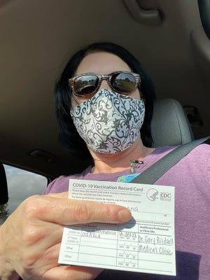 Raceland Middle School teacher Louanna Esponge holds up her COVID-19 vaccination card.