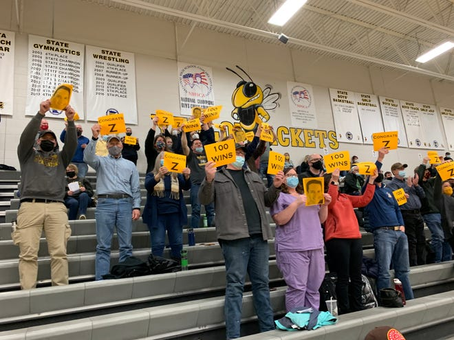 Crookston fans hold up signs celebrating coach Darin Zimmerman's 100th career win after the Pirates beat Perham, 60-43, on Thursday night.