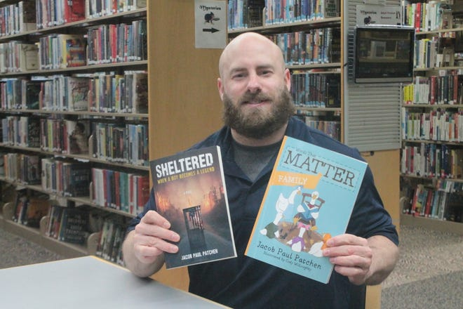 """Local author John Graham, who writes under the pen name of Jacob Paul Patchen, sits at the Crossroads Branch of The Guernsey County Public Library with his two latest book releases, """"Words that Matter: Family"""" and """"Sheltered: When a Boy Becomes a Legend."""""""