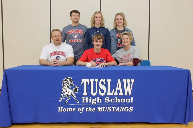 Tuslaw's Kaden Laum surrounded by family, signs his National Letter of Intent to play baseball at Malone. Lau is a three-sport star for the Mustangs, playing football, basketball and baseball.