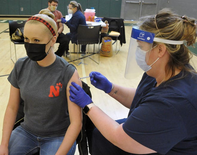 Kimberly Brentstuhl, of Norwayne Elementary, receives her COVID-19 injection Friday from Stacy Winkler of Drug Mart at Smithville High School.