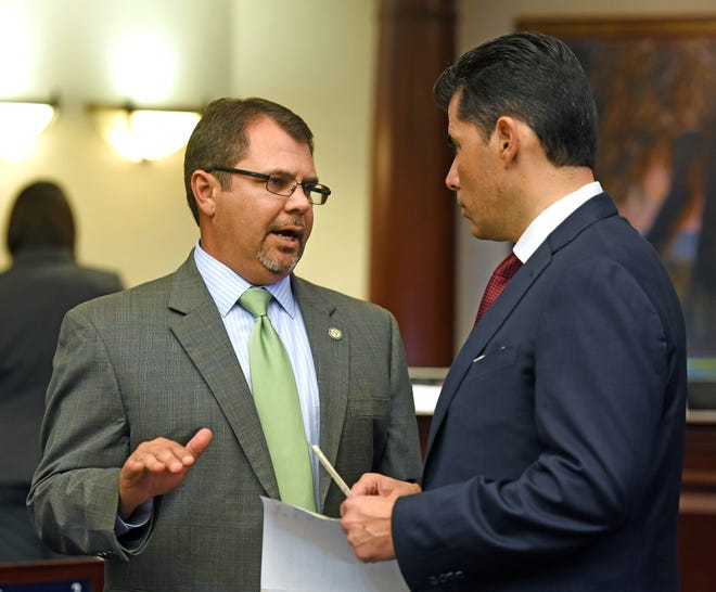 State Rep. Tom Leek, left, discusses House business with former House Speaker Jose Oliva during a previous legislative session.