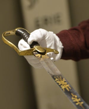 Hagen History Center Museum Educator Jeff Sherry holds a sword once owned by Commodore Oliver Hazard Perry.