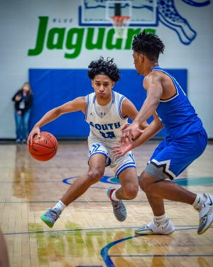 Blue Springs South guard Sonny McCreary, left, tries to dribble around Liberty defender Javion Byers in Thursday's game at South. The host Jaguars fell 82-64 in the regular season finale for their third straight loss.