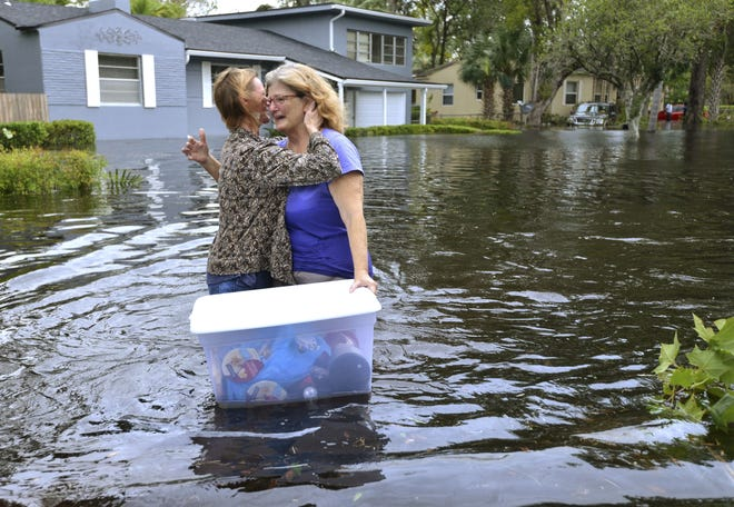 Charlotte Glaze gives Donna Lamb a teary hug as she floats out some of her belongings in floodwaters from the Ortega River in this 2017 photo in the aftermath of Hurricane Irma.