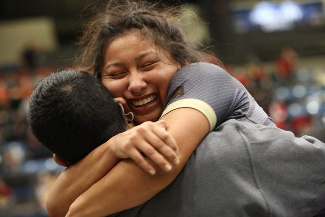 Garden City's Belle Hernandez gives her coach a hug after knocking off Blue Valley Southwest's Hannah Glynn in the 126-pound semifinals at Thursday's girls Division I state championships at Hartman Arena in Park City.
