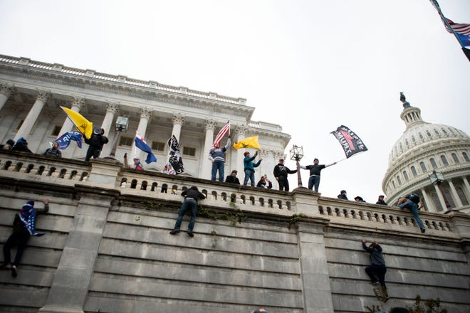 In this Wednesday, Jan. 6, 2021, file photo, supporters of President Donald Trump climb the west wall of the the U.S. Capitol on in Washington. Lies, misinformation and conspiracy theories related to the 2020 election are gaining traction among local, county and state Republicans, who are using their online platforms to disseminate many of the same dangerous messages that led to the violent insurrection at the Capitol last month. (AP Photo/Jose Luis Magana)