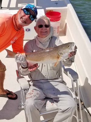 "Gil Walton, shown with his fishing guide, displays a redfish he has caught during the shooting of ""Growing Bolder's Ordinary People Living Extraordinary Lives."" It was the final fishing trip for Walton, who died Feb. 17."