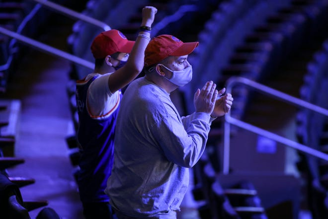 Fans cheer the New York Knicks coming out to warm up for an NBA basketball game against the Golden State Warriors on Tuesday, Feb. 23, 2021, in New York. A limited number of fans were allowed to attend.