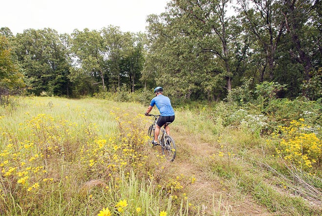 MDC has proposed regulations that would allow the expanded use of bicycles on most department-area service roads and add the allowance of electric bicycles. Shown is a cyclist on a trail at Canaan Conservation Area in Gasconade County.