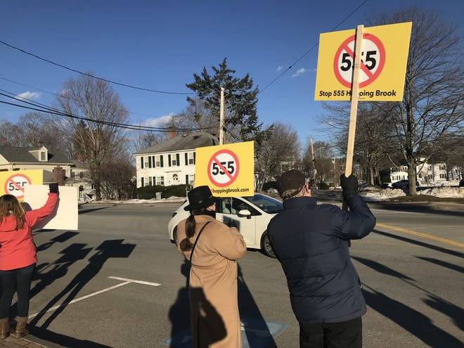 Over a dozen Medway and Holliston residents gathered outside Holliston Town Hall on Thursday afternoon to oppose the 555 Hopping Brook project proposal.