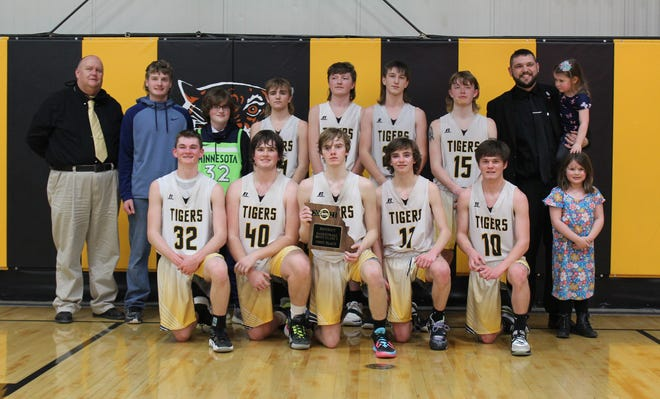 The 2020-21 Higbee High School boys basketball team won the Class 1 District 10 tournament championship, the school's first of its kind in athletic history, by defeating Community R-VI of Laddonia Thursday by a 61-31 result at home. Team members are (wearing white jerseys, left to right) Jordan Fuemmeler, Jamie Smith, Keetun Redifer, Derek Rockett and Luke Ritter. Second row players are Chevy Grimsley, Will Spilman, Jaxon Hudson and Chad Crawford. Head coach Tanner Burton is shown second row right holding his daughter, and assistant coach David Roush (second row, left).