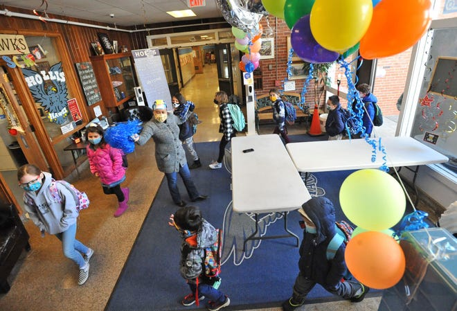 Hollis School English Language Learner teacher Jackie Gonzalez greets students as they enter the decorated lobby to kick off the 100th day of school celebration in Braintree, Friday, Feb. 26, 2021.