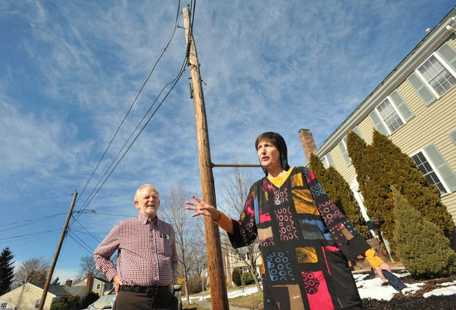 Donna Halper, right, voices her frustration with frequent power outages in her North Quincy neighborhood as her husband Jon Jacobik looks on.