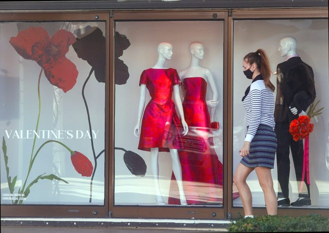 A woman strolls past a Saks Fifth Avenue window display on Worth Avenue a week before Valentine's Day.