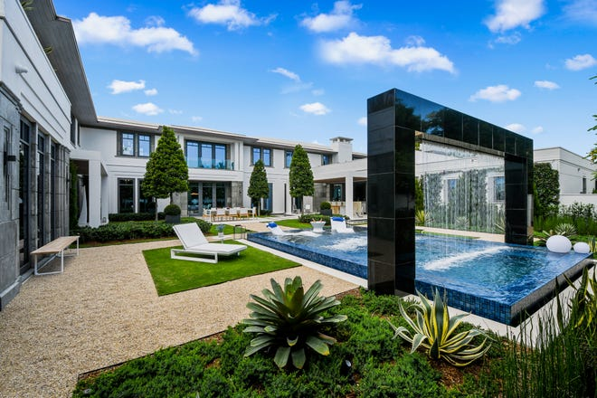 The courtyard at 520 Island Road is a centerpiece between living, bedroom and family spaces and features a pool with a 'rain wall.'  The home is being sold as a 'turnkey' property.