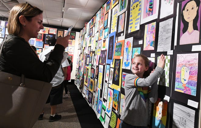 Kelly Wargnier takes a photo of her daughter Brooklyn Wargnier, of Brookside Elementary, as she holds her hand below a drawing of a hand, part of a Robert T. McKee Student Art Exhibition project from her teacher, Roz Lopez, on March 16, 2019. This year's exhibition will be virtual.