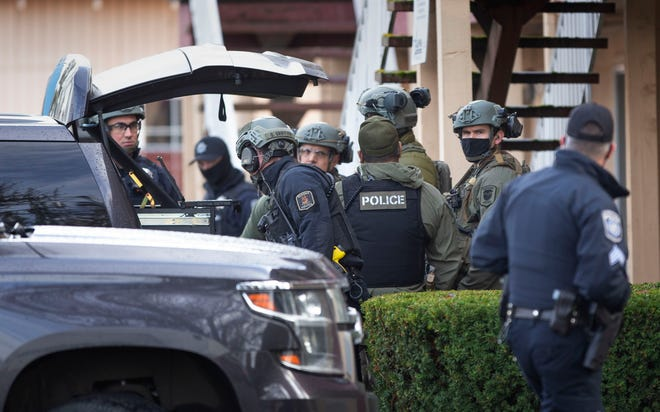 A Eugene police SWAT team meets behind the Econo Lodge at West Seventh Avenue and Tyler Street during a standoff in the nearby parking lot Friday morning.